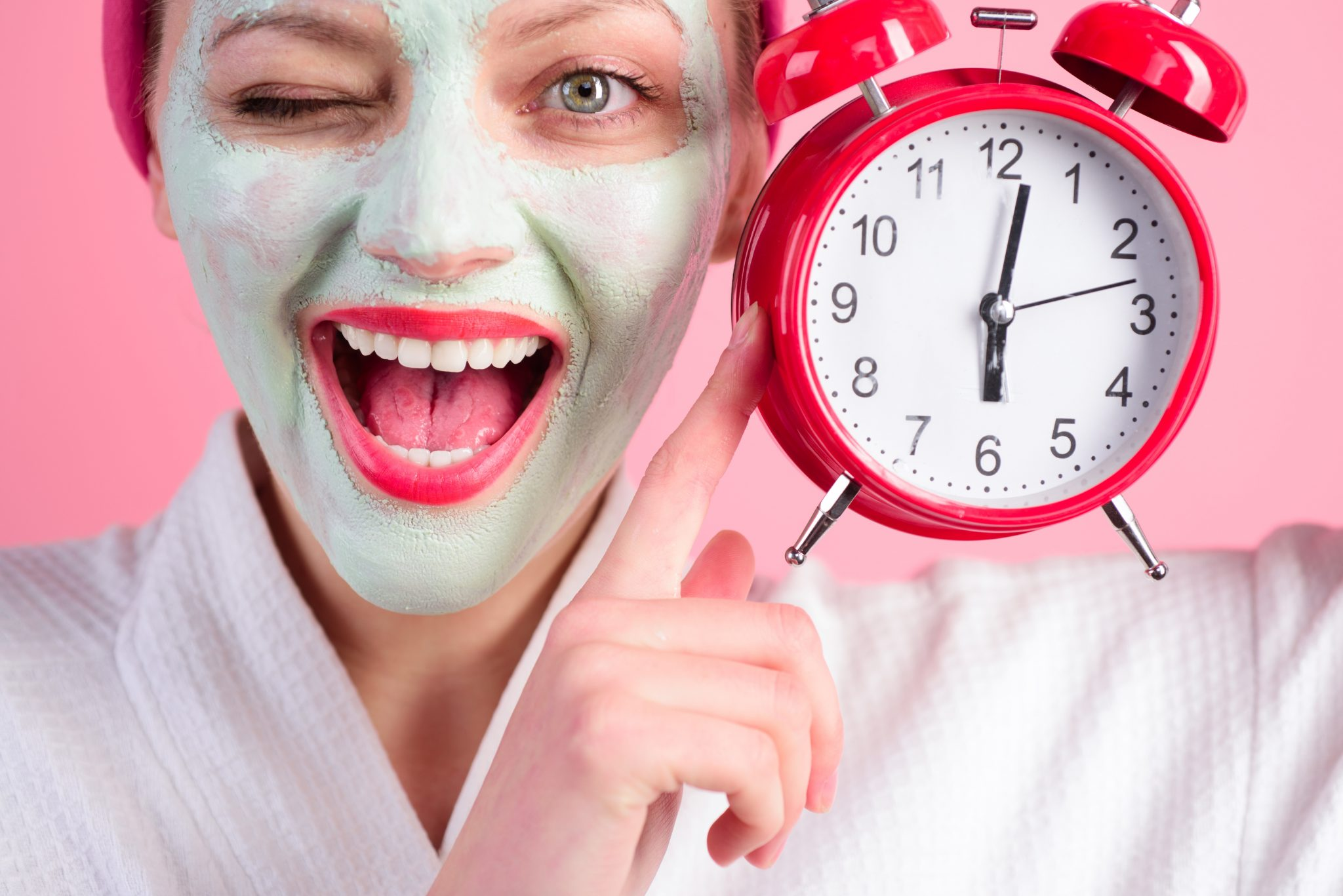 Facial cosmetical mask. Spa. Cosmetic procedures. Woman with cosmetic mask on face holds clock. Wellness and Spa concept. Happy woman with facial mask. Close up portrait.